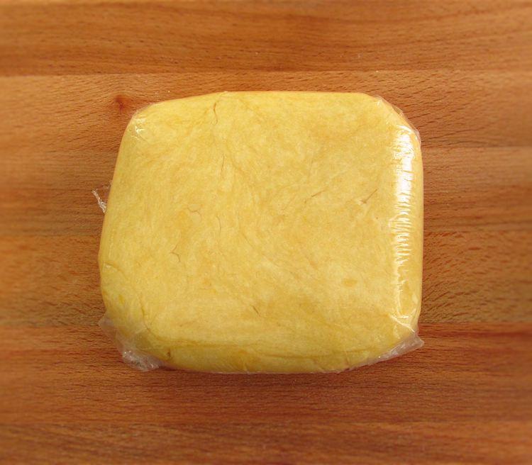 Massa de tarte embrulhado em película aderente numa tábua de madeira