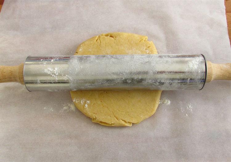 Massa de tarte com um rolo da massa polvilhado com farinha