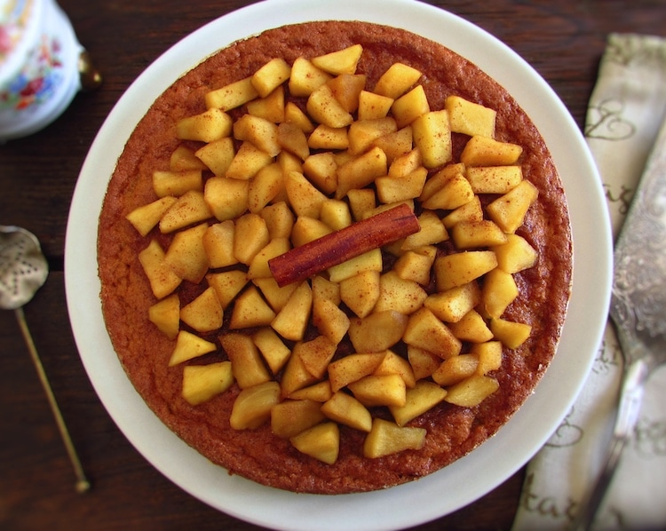 Vanilla cake topped with caramelized apple on a plate