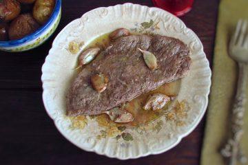 Bifes no forno com batatas com casca num prato