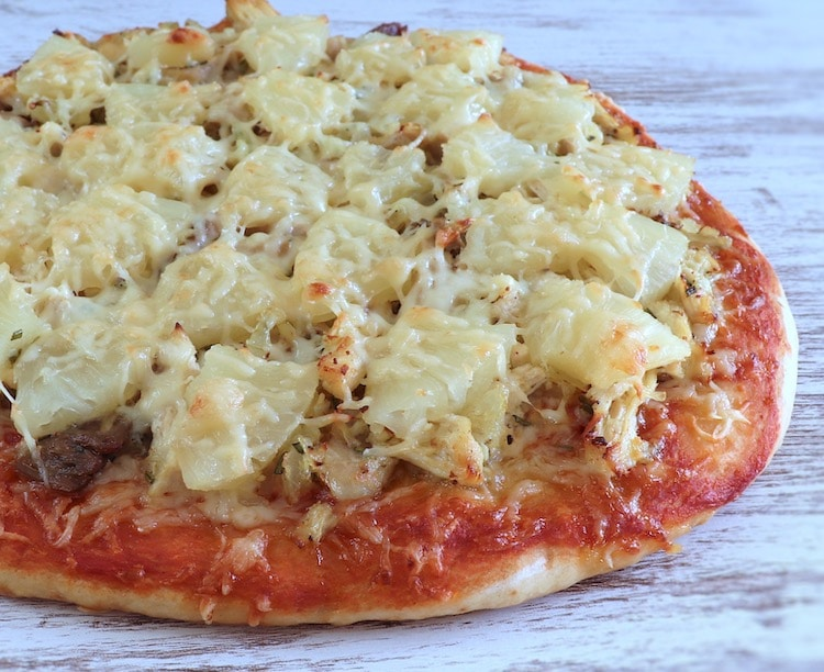 Chicken and pineapple pizza on a table
