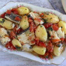 Cod with onion and tomato in the oven on a platter