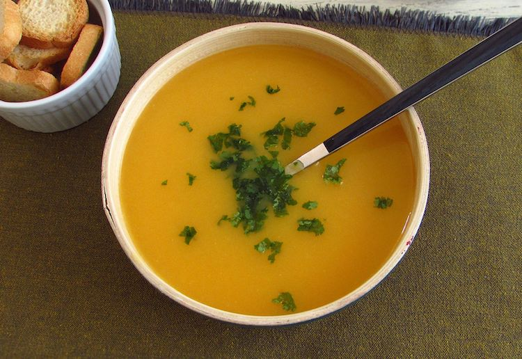 Creamy carrot soup with orange on a soup bowl