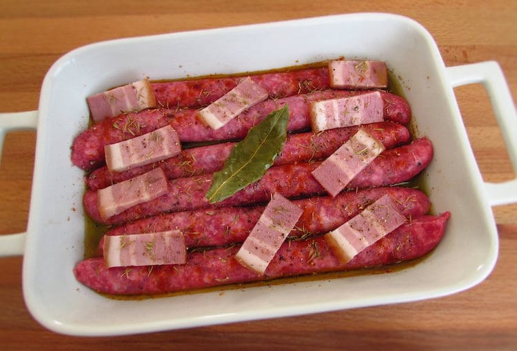Sausages and bacon seasoned with salt, pepper, nutmeg, paprika, thyme and bay leaf on a baking dish