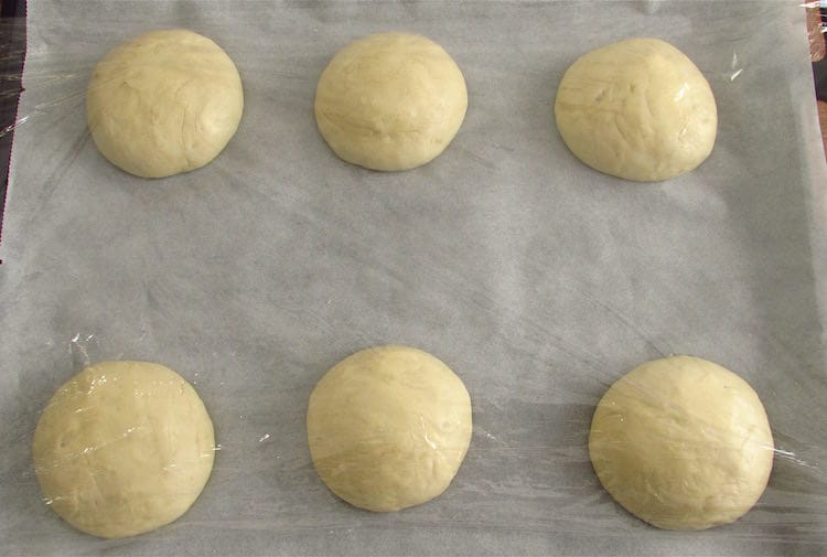 Garlic bread dough divided in six balls on a baking tray lined with tracing paper and covered with cling film