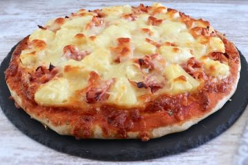 Ham and pineapple pizza on a table