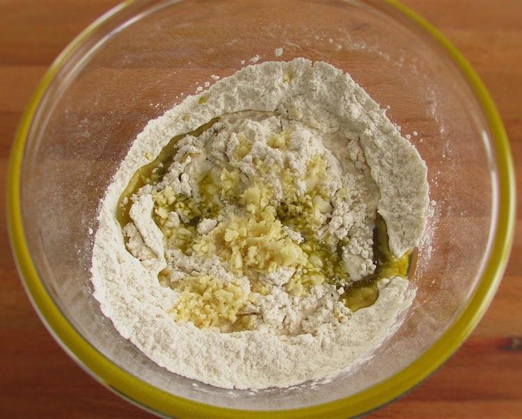 Mistura de farinha, sal e fermento de padeiro com azeite, alhos picados e água numa taça de vidro