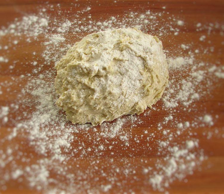 Massa de pão de alho polvilhada com farinha numa mesa de madeira