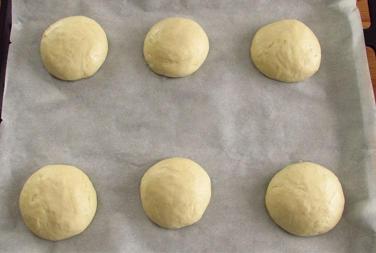Massa de pão de alho dividida em seis num tabuleiro forrado com papel vegetal