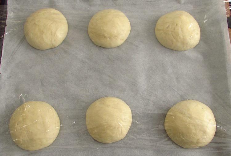 Massa de pão de alho dividida em seis num tabuleiro forrado com papel vegetal e coberta com película aderente