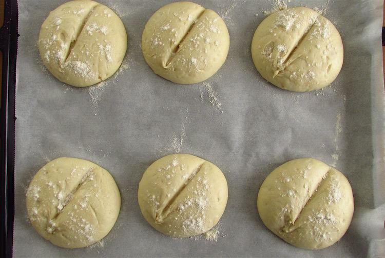 Massa de pão de alho dividida em seis polvilhada com farinha num tabuleiro forrado com papel vegetal