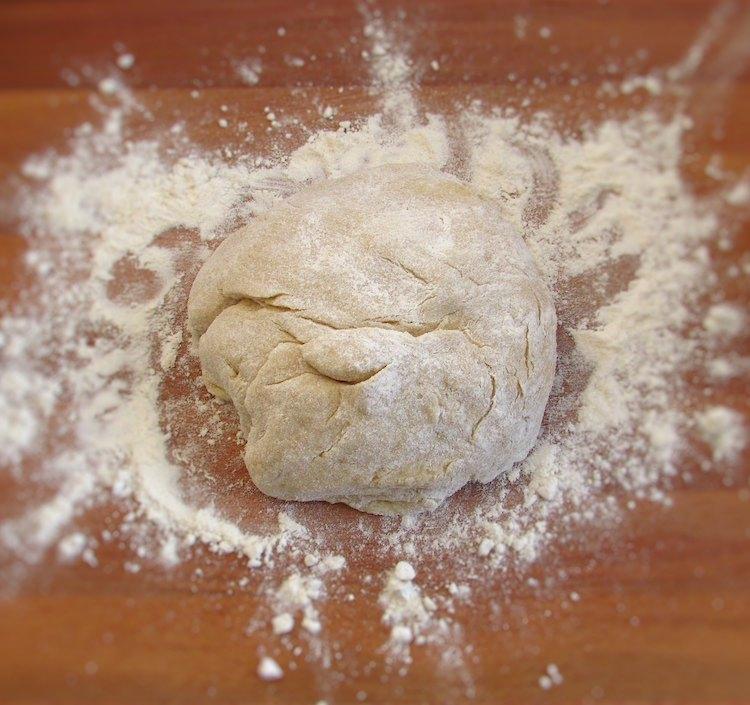 Massa de pão de leite polvilhada com farina numa mesa de madeira