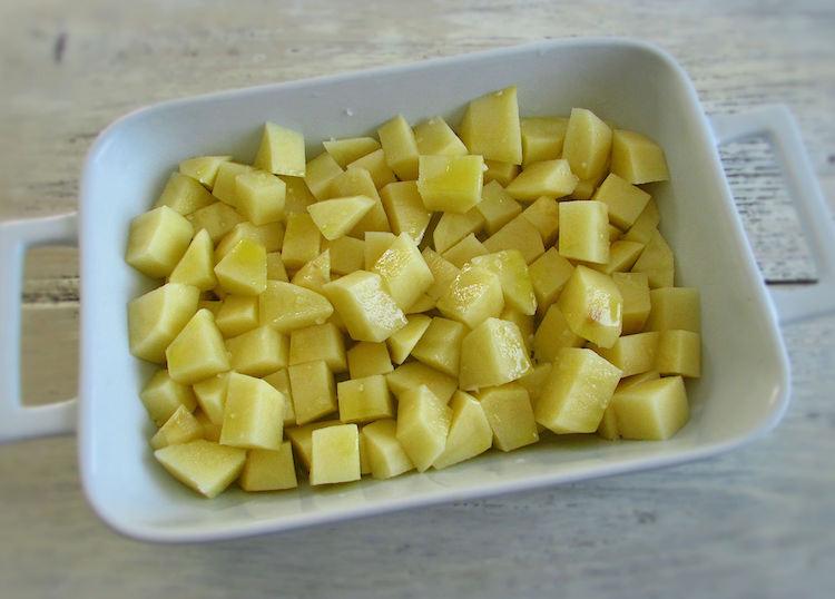 Batatas numa assadeira regadas com azeite e temperadas com sal