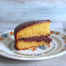 Fatia de bolo de laranja com cobertura de chocolate num prato