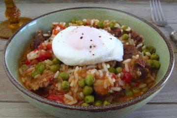 Carne estufada com arroz e ovos escalfados num prato fundo