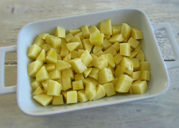 Potatoes on a baking dish drizzled with olive oil and seasoned with salt