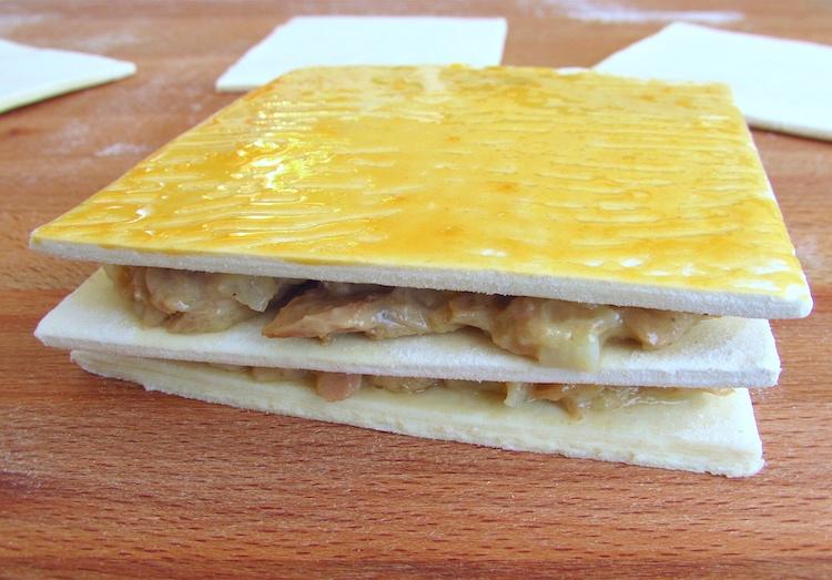 Massa folhada recheada com uma mistura de atum e pincelada com gema de ovo baitda numa tábua de madeira