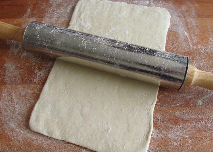 Massa folhada numa mesa de madeira polvilhada com farinha
