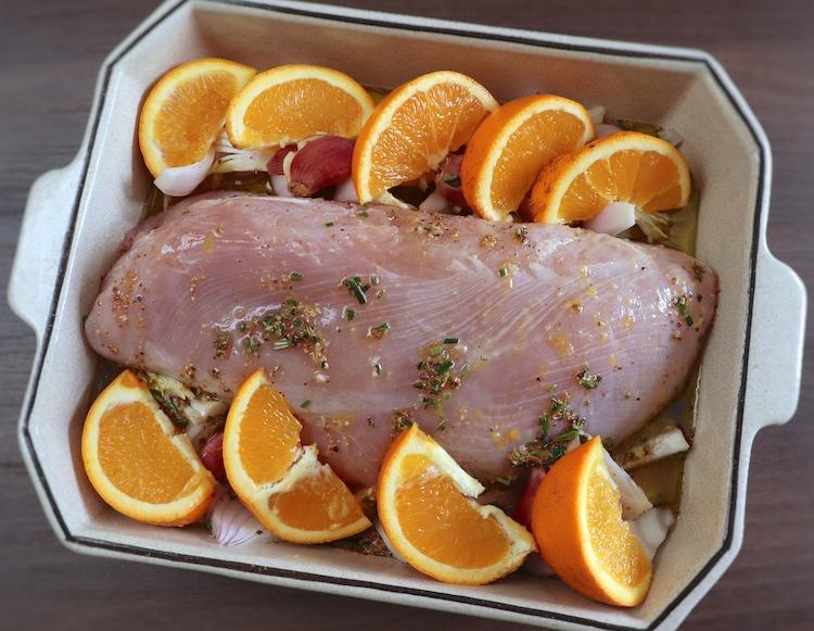 Lombo de peru temperado com sal, alhos com casca esmagados, cebola descascada cortada em fatias, sumo de laranja, pimenta, noz-moscada, alecrim, sumo de laranja e azeite numa assadeira