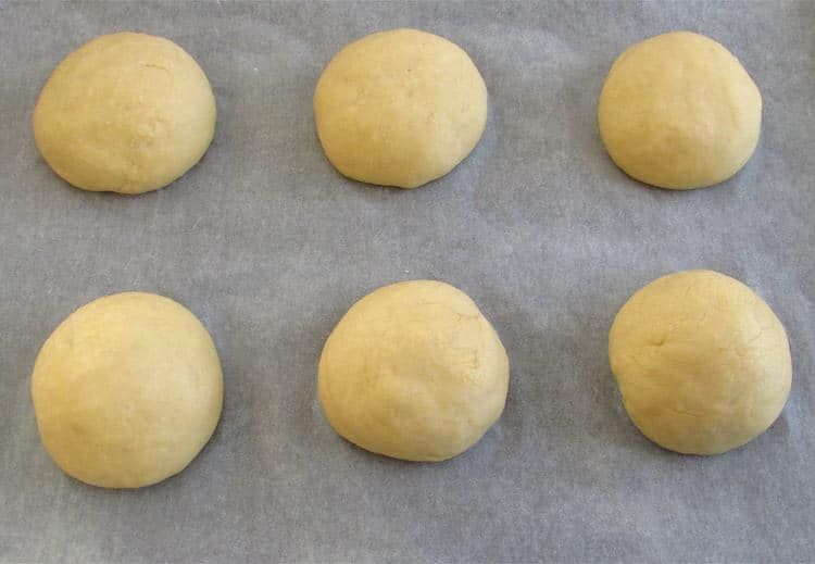 Milk bread dough on a baking tray lined with tracing paper