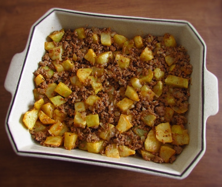 Meat and potatoes on a baking dish