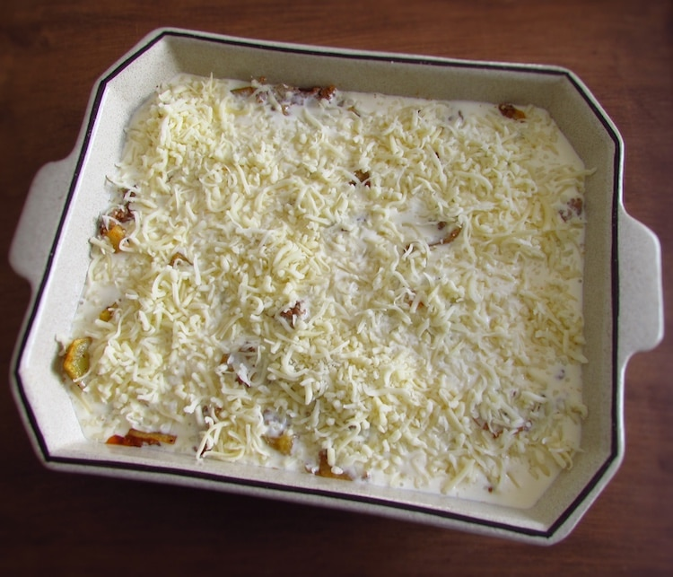 Meat and potatoes drizzled with a béchamel mixture, sprinkled with grated cheese on a baking dish