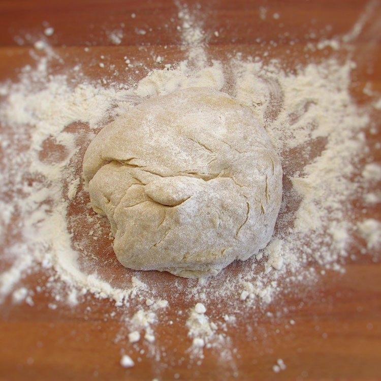 Massa de pão de leite numa tábua de madeira polvilhada com farinha