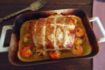 Pork loin in the oven with shrimp on a baking dish