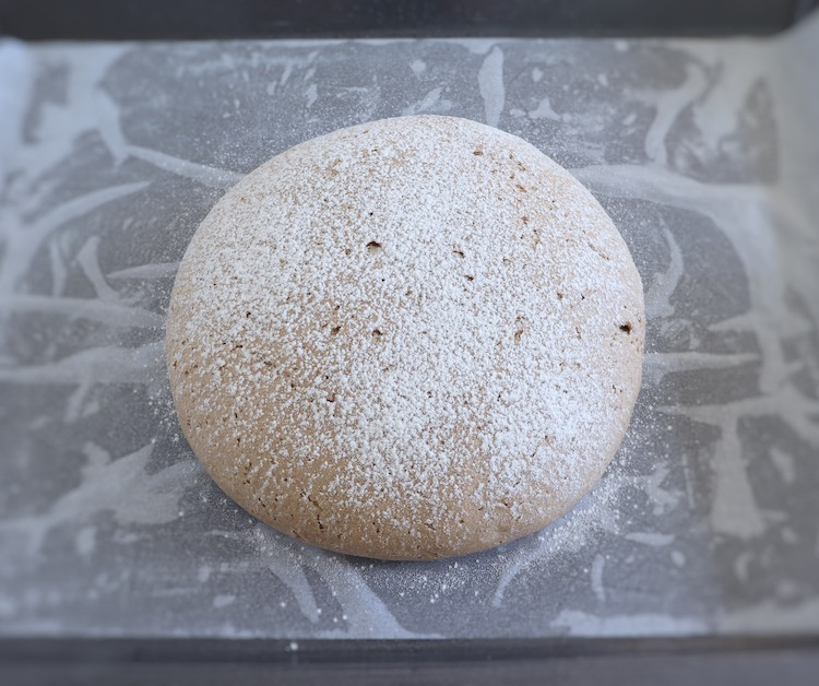 Rye bread dough on a baking tray lined with parchment paper