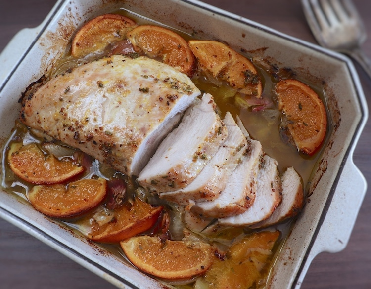 Slices of turkey loin with orange on a baking dish