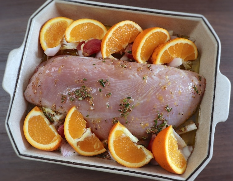 Turkey loin seasoned with salt, peeled onions cut into slices, unpeeled crushed garlic, orange juice, pepper, nutmeg, rosemary, cinnamon, orange juice and olive oil on a baking dish