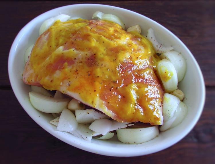 Pork leg seasoned with salt, pepper, nutmeg, saffron, honey, peeled garlic, onion cut in half moon slices and mustard on a baking dish