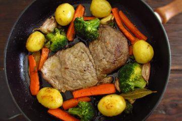 Bifes com batatas e legumes salteados numa frigideira