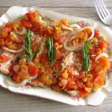 Bifes de peru no forno com tomate numa assadeira