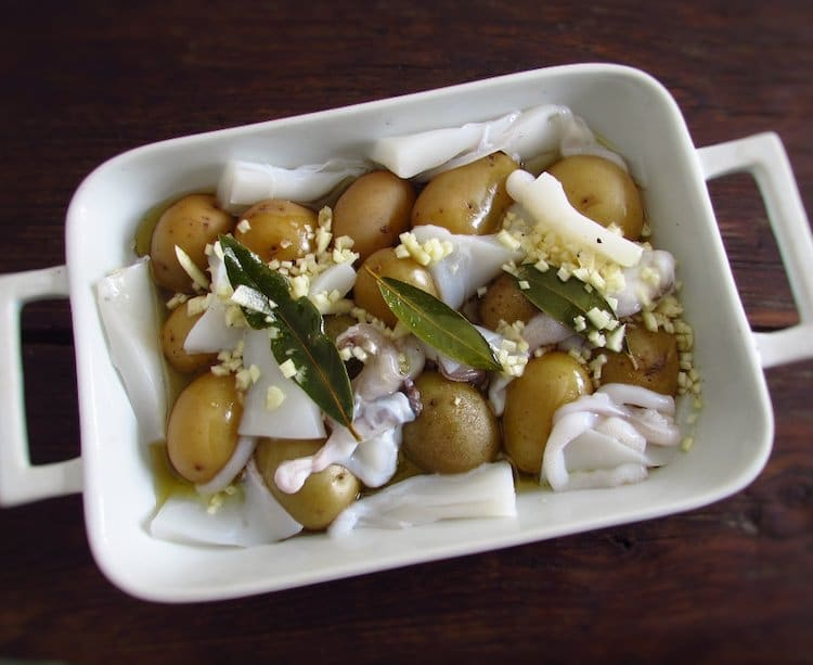 Potatoes and cuttlefish on a baking dish drizzled with olive oil