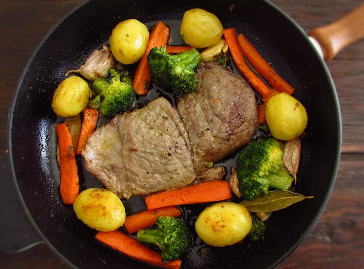 Steaks with potatoes and sautéed vegetables on a frying pan