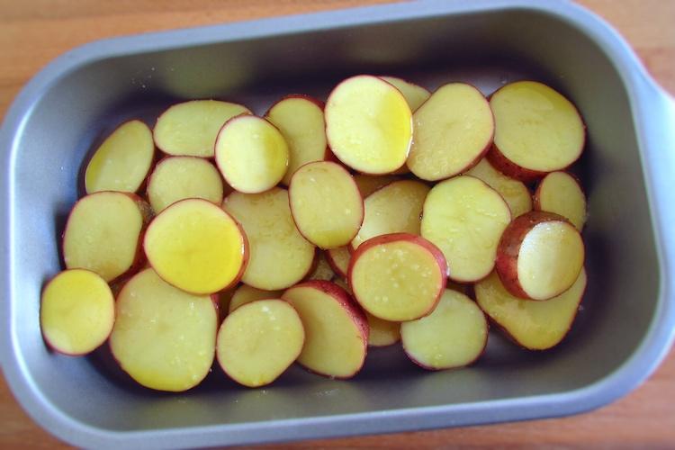 Batatas às rodelas temperadas com sal e azeite numa assadeira