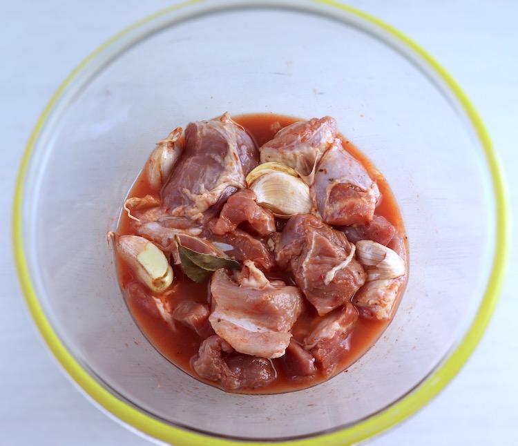 Carne de porco temperada com sal, pimenta, alhos com casca esmagados, massa de pimentão, louro e vinho branco numa taça de vidro
