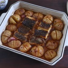 Cod in the oven with potatoes, olive oil and lemon on a baking dish