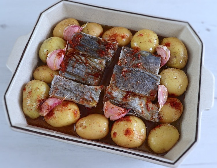 Cod with potatoes seasoned with lemon juice, unpeeled crushed garlic, salt, pepper, paprika and olive oil on a baking dish