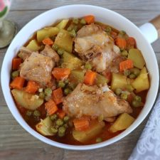 Stewed rabbit with potatoes, peas and carrots on a dish bowl