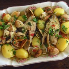 Wreckfish in the oven with clams on a platter
