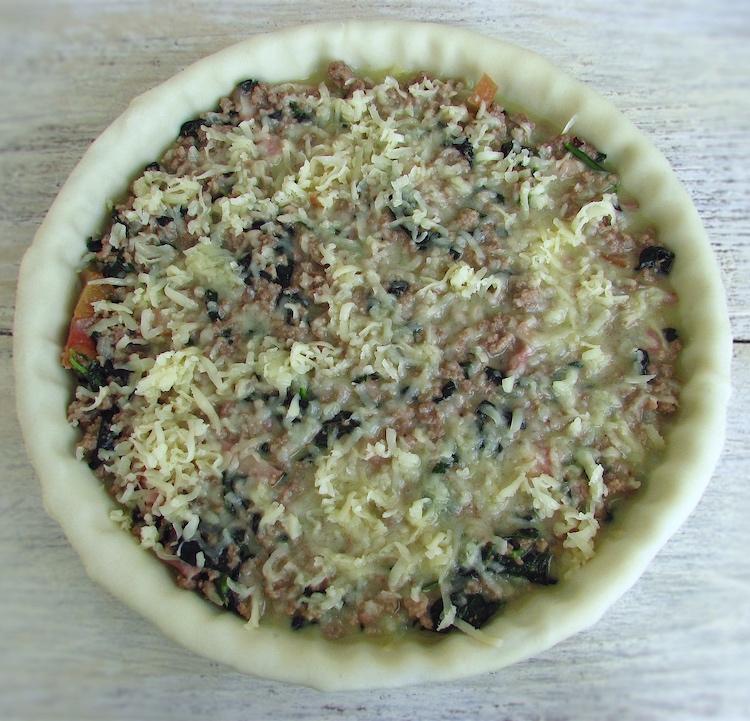 Tarteira forrada com massa folhada e recheada com carne e queijo ralado