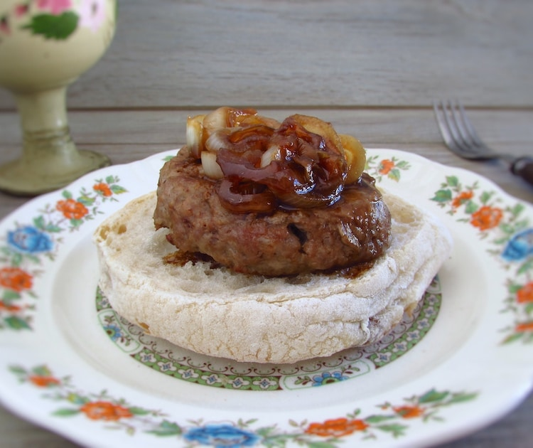 Burger with caramelized onion with a bread slice on a plate