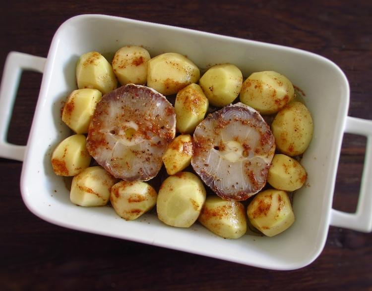 Peixe e batatas numa assadeira temperados com um pouco de sal, pimenta, noz-moscada, pimentão doce e sumo de limão