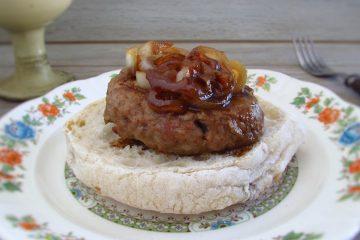 Hambúrgueres com cebola caramelizada com uma fatia de pão num prato