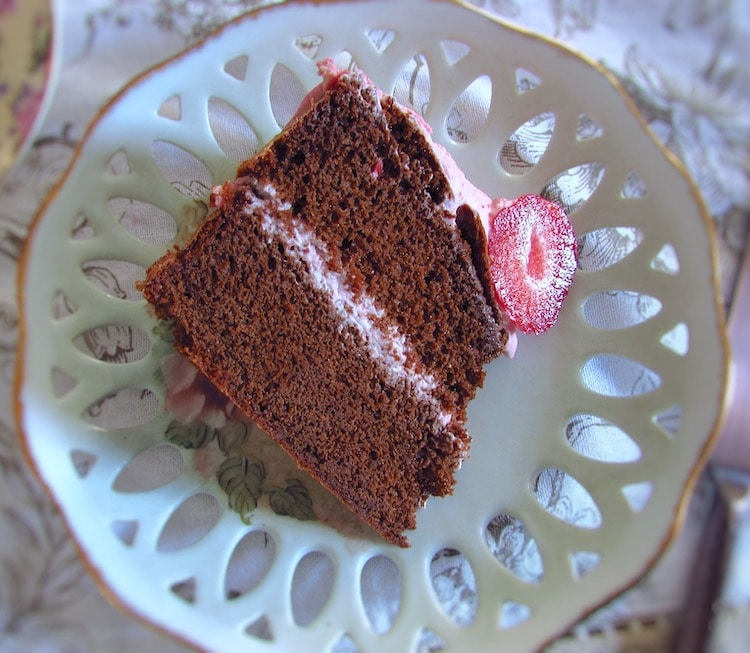 Slice of chocolate cake with strawberry cream on a plate