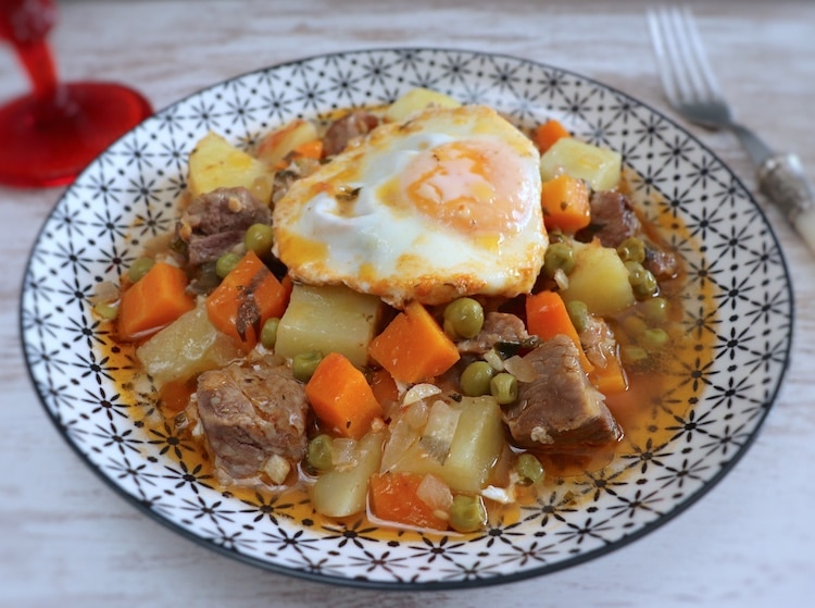Stewed meat with potatoes and poached eggs on a plate