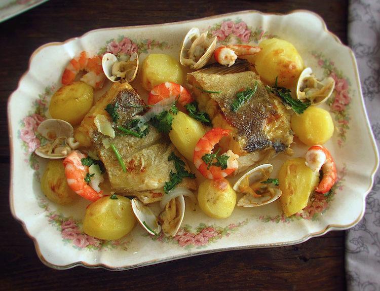 Bacalhau no forno com camarão e amêijoas numa travessa
