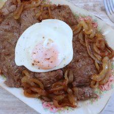 Bifes fritos com ovo estrelado numa travessa